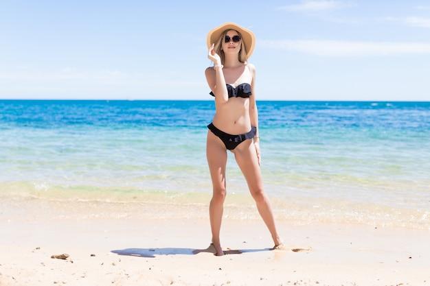 Schöne frau in sonnenbrille und hut mit perfektem körper im sexy bikini über strand