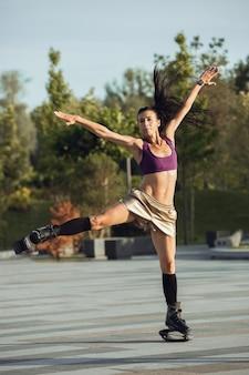 Schöne frau in sportbekleidung, die an einem sonnigen sommertag in einem kangoo springt, springt schuhe auf der straße