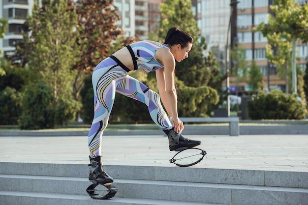 Schöne frau in sportkleidung, die in einem kangoo springt, springt schuhe