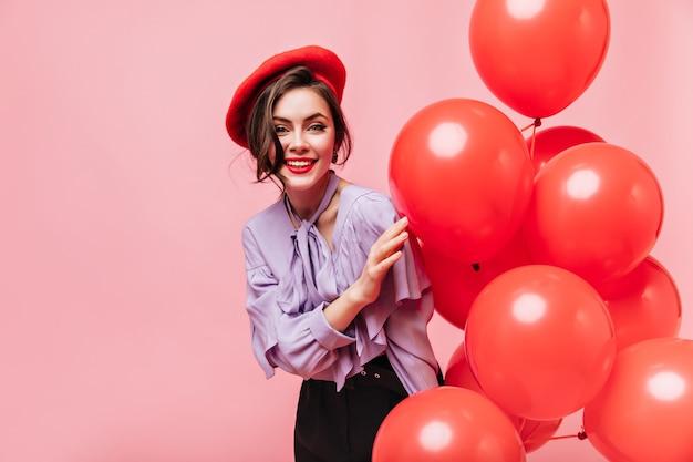 Schöne frau in stilvoller bluse und baskenmütze schaut in die kamera mit lächeln. porträt des mädchens mit den roten lippen, die mit luftballons aufwerfen.