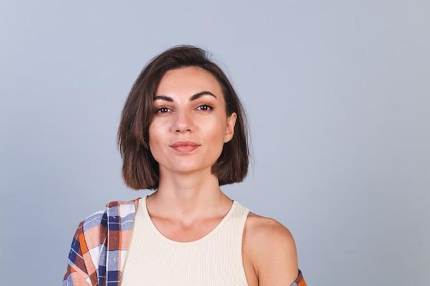 Schöne frau in top und kariertem hemd an grauer wand mit make-up positivem selbstbewusstem lächeln, glücklichen emotionen