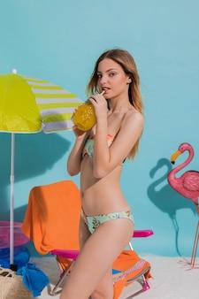 Schöne frau in trinkendem cocktail des bikinis