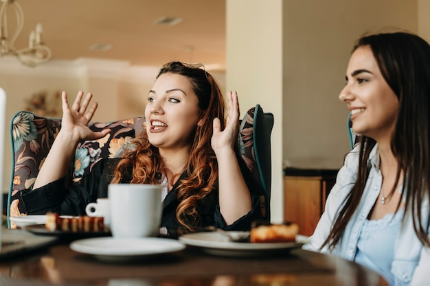 Schöne frau in übergröße mit roten haaren, die geschichten erzählt, während sie mit ihrer freundin in einem café sitzt.
