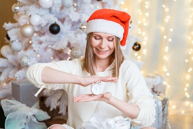 Schöne frau in weihnachtsmütze hält einen wecker und lächelt süß vor dem hintergrund der festlichen weih...