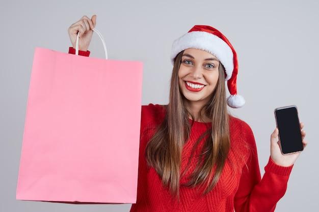 Schöne frau in weihnachtsmütze, roter pullover, halten pakete mit einkäufen und handy. konzept für weihnachten online-verkauf, bestellung, lieferung.