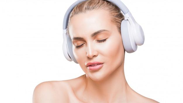 Schöne frau in weißen kopfhörern hört musik mit geschlossenen augen auf weißer wand