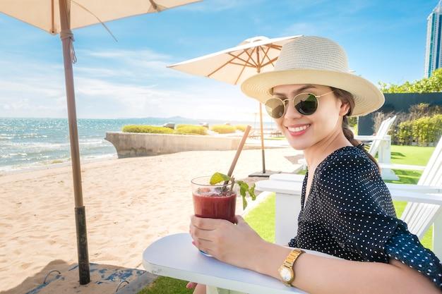 Schöne frau ist entspannend am strand, unter sonnenschirm