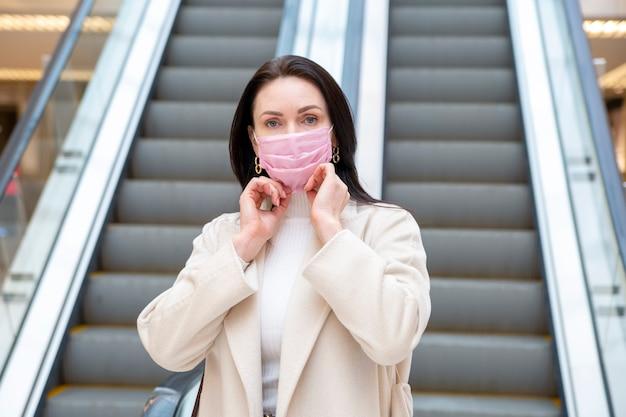 Schöne frau korrigiert rosa medizinische maske auf ihrem gesicht vor dem hintergrund der rolltreppe im einkaufszentrum oder flughafen.schutzkonzept