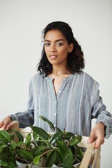Schöne frau lächelnde haltebox mit pflanzen in blumentöpfen