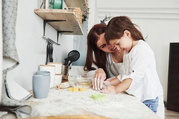 Schöne frau lächelt. glückliche tochter und mutter bereiten zusammen backwaren zu. kleiner helfer in der küche