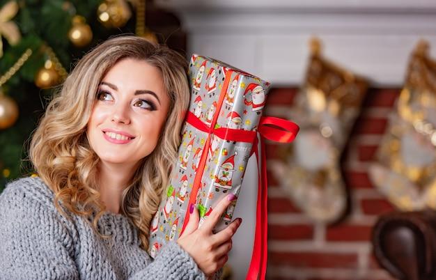 Schöne frau lächelt und hält geschenk für neujahr in der hand in der nähe von kopf und posen.