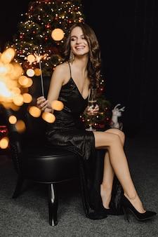 Schöne frau lächelt und hält wunderkerze und ein glas mit champagner