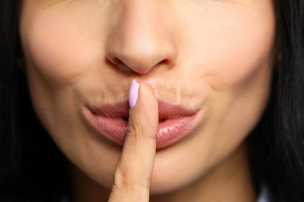 Schöne frau legte ihren finger auf geschlossene rote lippen