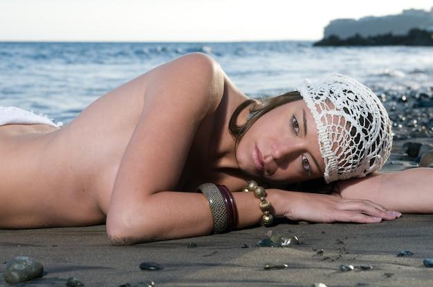 Schöne frau liegt am strand im sand