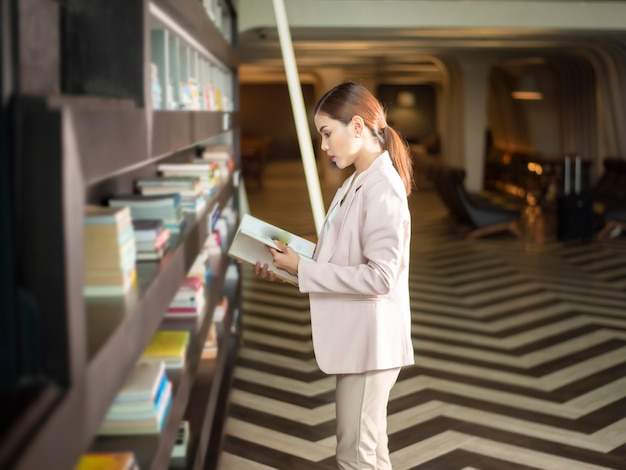 Schöne frau liest bücher in der bibliothek
