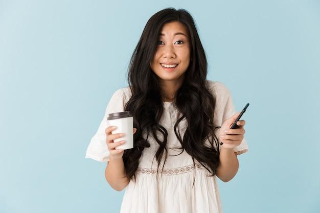 Schöne frau lokalisiert über blaue wand, die kaffee hält, der per telefon chattet
