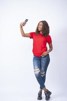 Schöne frau macht ein selfie mit ihrem handy