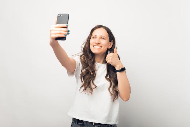 Schöne frau macht ein selfie mit ihrem telefon, während sie den daumen zeigt.