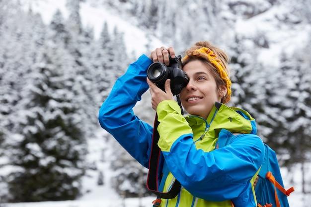 Schöne frau macht foto auf professioneller kamera