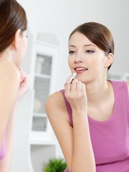 Schöne frau malt ihre lippen mit lippenstift, der in den spiegel zu hause schaut