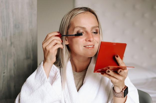 Schöne frau malt ihre wimpern mit mascara und schaut in einen kleinen spiegel.