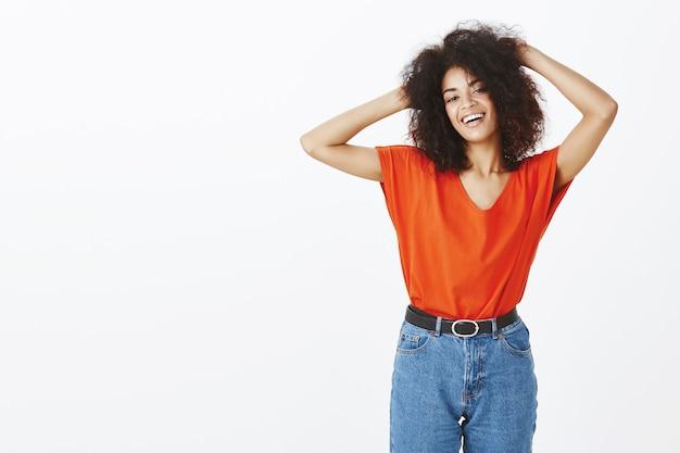 Schöne frau mit afro-frisur, die im studio aufwirft