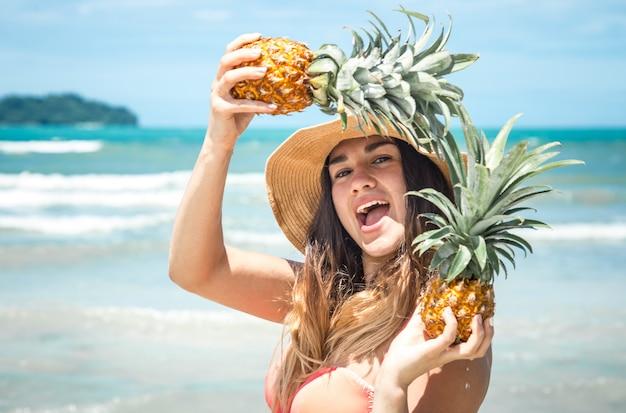 Schöne frau mit ananas an einem exotischen strand, eine fröhliche stimmung und ein schönes lächeln