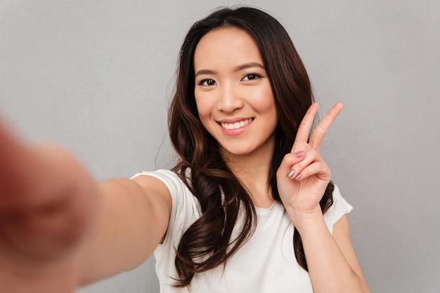 Schöne frau mit asiatischem aussehen, das selfie nimmt und siegeszeichen mit perfektem lächeln zeigt, lokalisiert über graue wand