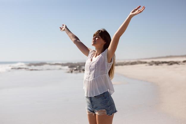 Schöne frau mit ausgestreckten armen am strand im sonnenschein stehen