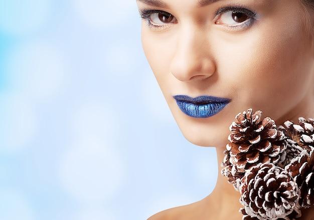 Schöne frau mit blauen lippen und tannenzapfen
