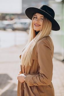Schöne frau mit blondem haar, das schwarzen hut trägt