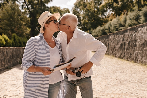 Schöne frau mit blondem hemdhaar im hut und lang gestreifter bluse, die mit grauem mann im weißen langarmhemd mit kamera im freien küsst.