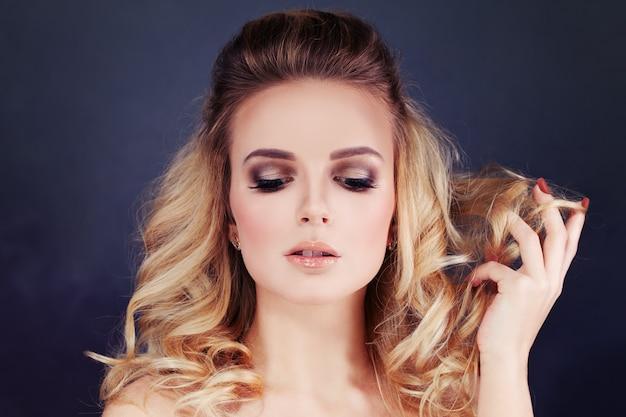 Schöne frau mit blonden haaren. lockige frisur und make-up