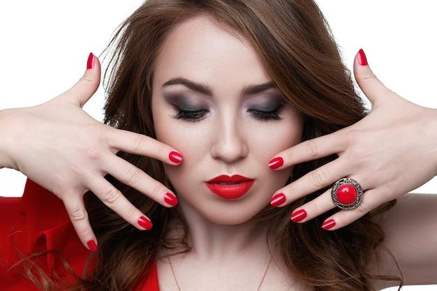 Schöne frau mit blonden haaren. model mit rotem lippenstift und roten nägeln. porträt des glamourmädchens mit hellem make-up. schönheit weibliches gesicht. perfekte haut und make-up. rote lippen und nagellack