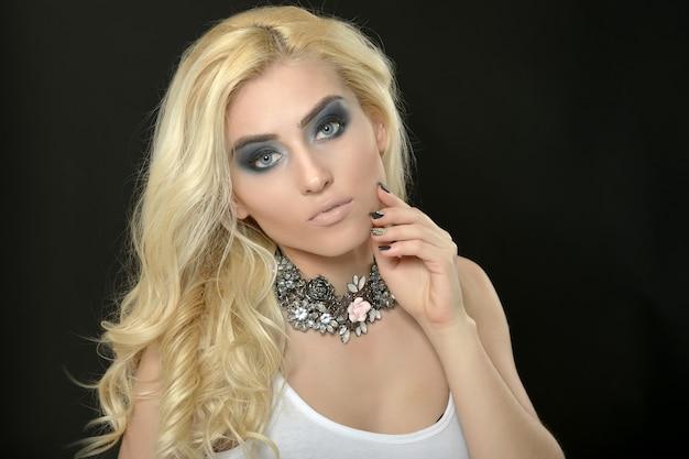 Schöne frau mit blonden haaren und make-up auf schwarzem hintergrund