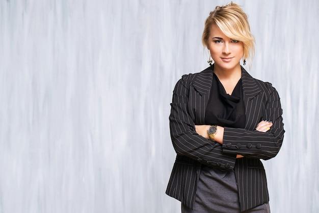 Schöne frau mit blonden haaren und schwarzem anzug