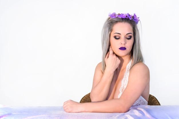 Schöne frau mit blumenkranz und violettem make-up