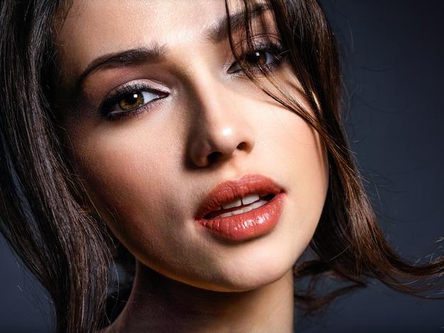 Schöne frau mit braunen haaren. attraktives modell mit braunen augen. model mit einem rauchigen make-up. nahaufnahmeporträt einer hübschen frau betrachtet kamera.