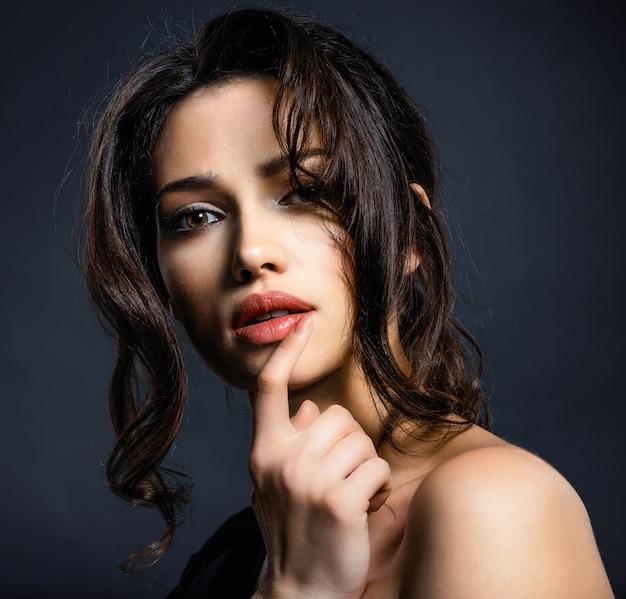 Schöne frau mit braunen haaren. attraktives modell mit braunen augen. model mit einem rauchigen make-up. nahaufnahmeporträt einer hübschen frau. kreative frisur.