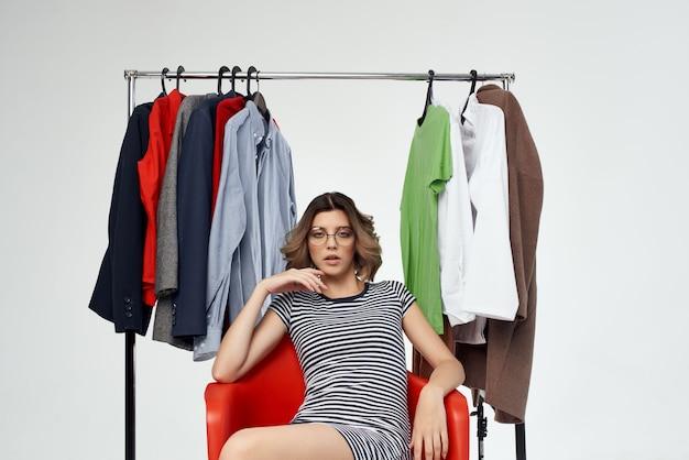 Schöne frau mit brille, die auf bekleidungsgeschäft shopaholic isolierten hintergrund anprobiert. foto in hoher qualität