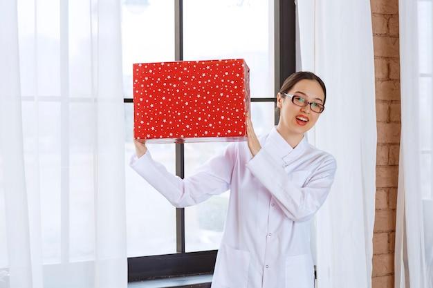Schöne frau mit brille im laborkittel, die große geschenkbox in der nähe des fensters hält.