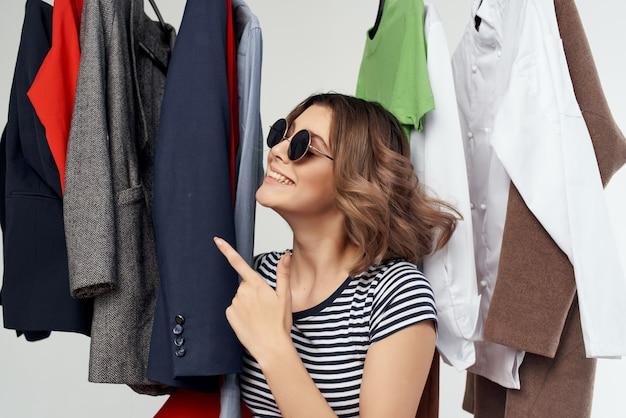 Schöne frau mit brille neben kleidung modespaß isolierten hintergrund