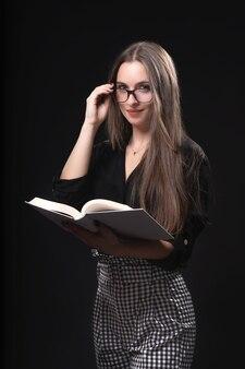 Schöne frau mit brille und buch auf schwarzem hintergrund