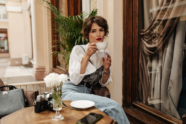 Schöne frau mit brünettem haar im weißen hemd hält tasse tee im café. stilvolle frau mit roten lippen und jeans mit gürtel sitzt im restaurant.