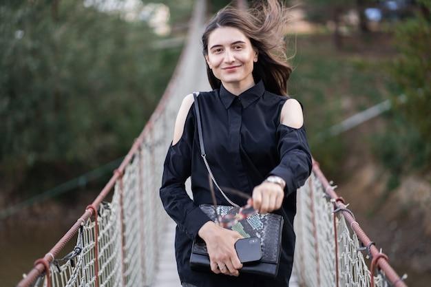 Schöne frau mit brünetten haaren in dunkler kleidung und sonnenbrille. mode straßenfotografie. modemodell steht auf hängebrücke auf naturhintergrund.