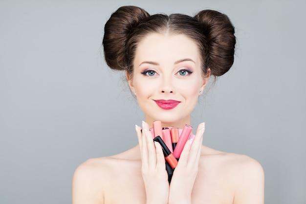 Schöne frau mit bunten lippenstiften mode-make-up-konzept
