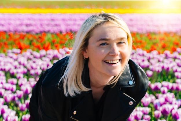 Schöne frau mit dem blonden haar, das in den bunten tulpenblumenfeldern in der region amsterdam steht