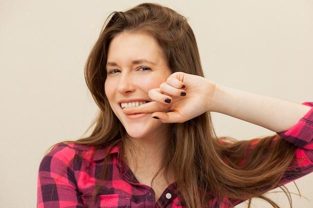 Schöne frau mit dem finger auf die zähne