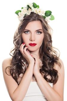 Schöne frau mit dem gelockten haar lokalisiert auf weißem hintergrund. porträt eines sexy models mit hellem make-up und rosenblüten