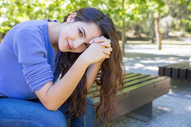 Schöne frau mit dem gesunden haar, das auf bank im park sitzt